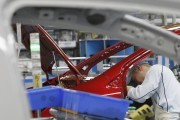 A worker assembles a Toyota Motor Co's new Corolla vehicle at a production line following a line-off ceremony in Ohira village of Miyagi prefecture