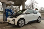 The 2015 BMW i3 fills up at a gas station.