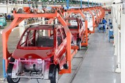Workers assemble electric automobiles at a workshop in Qingzhou City