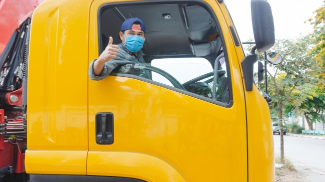 photos of truck drivers wearing masks to protect against dust and the spread of the flu. Covid 19. Inside the car front.